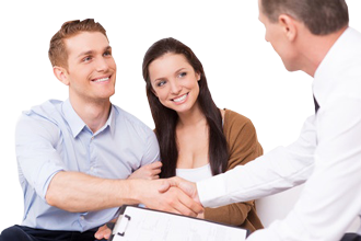 Happy young man shaking hand to financial agent while sitting together with his wife.